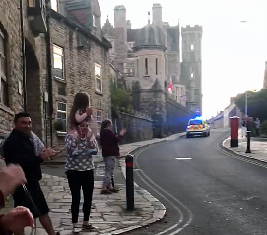 Police car being clapped as it drives through Swanage.