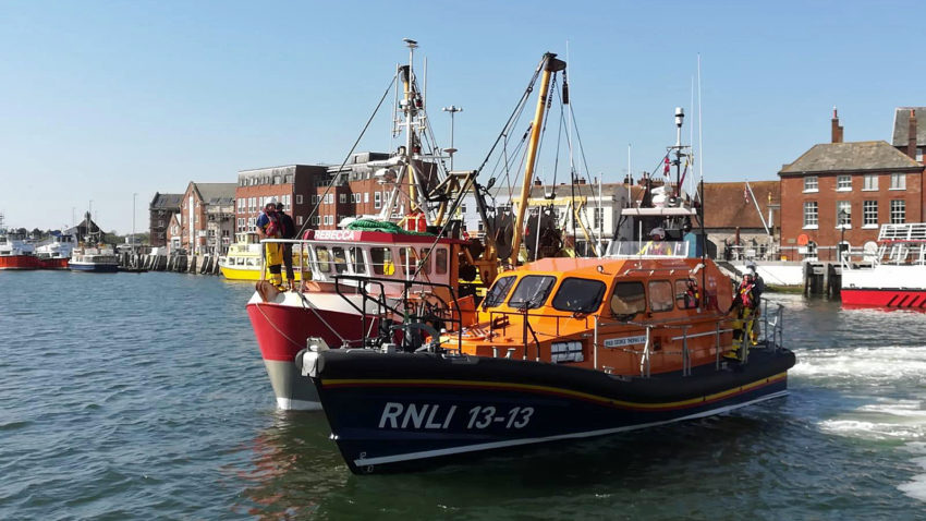 Swanage lifeboat in Poole Harbour with rescued fishing boat