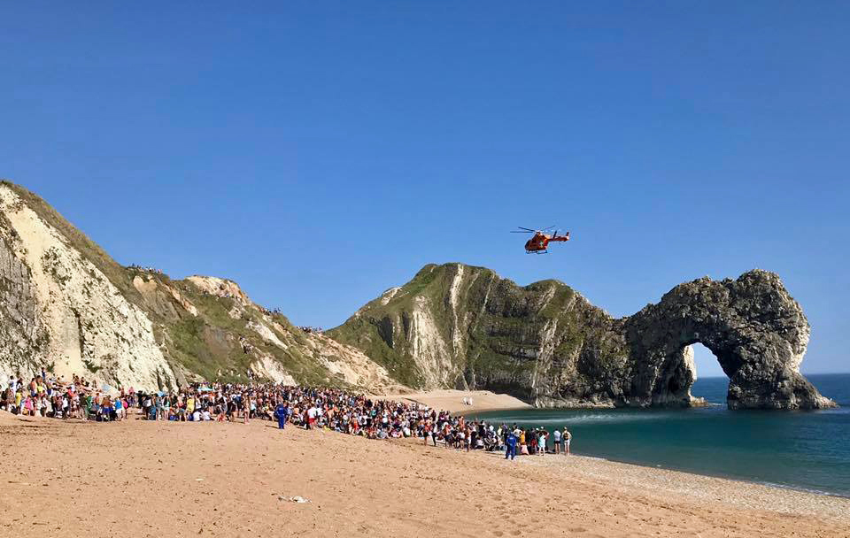Beach crowds make way for a second helicopter to land on the beach