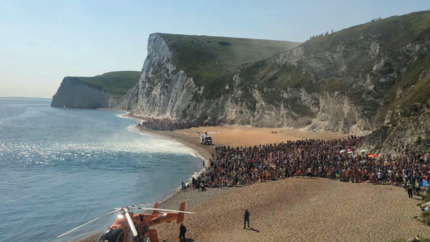 People herded together on Durdle Door beach