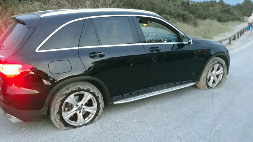 Car with burst tyres in Studland