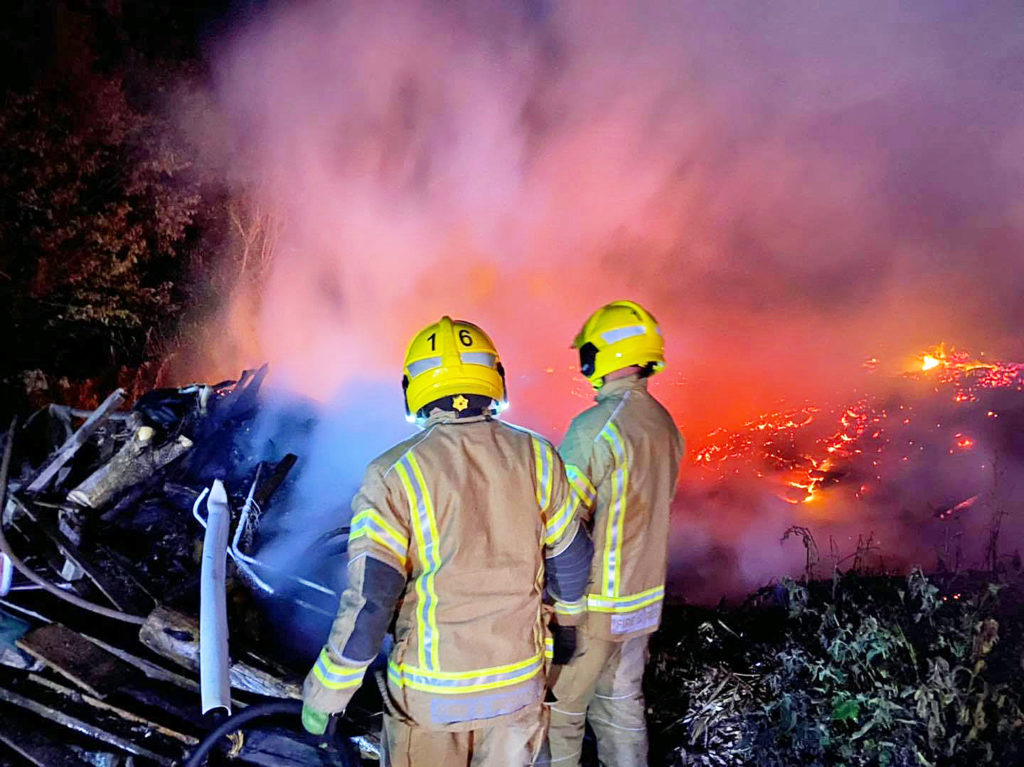 FirefigFirefighters fighting farmyard fire