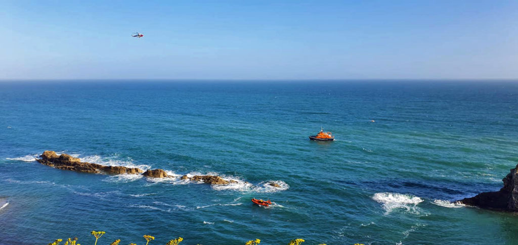 The RNLI and coastguard helicopter searching for a missing swimmer
