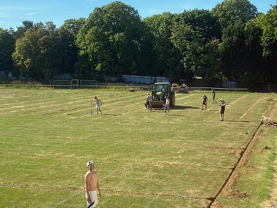 Volunteers help install the new drainage to the pitch