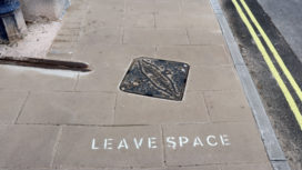 'leave space' sign on a pavement