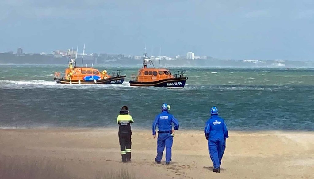 Coastguard on beach as lifeboat rescues paddleboarders.
