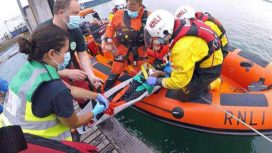 Poole Lifeboat crew rescuing injured woman