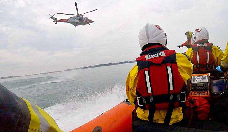 Poole Lifeboat crew rescue with Coastguard rescue helicopter