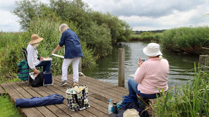 Artists painting by a river