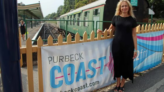 Michelle Langthorne standing by the Purbeck Coast banner