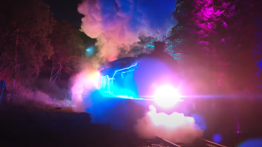 Steam train lit up with coloured lights