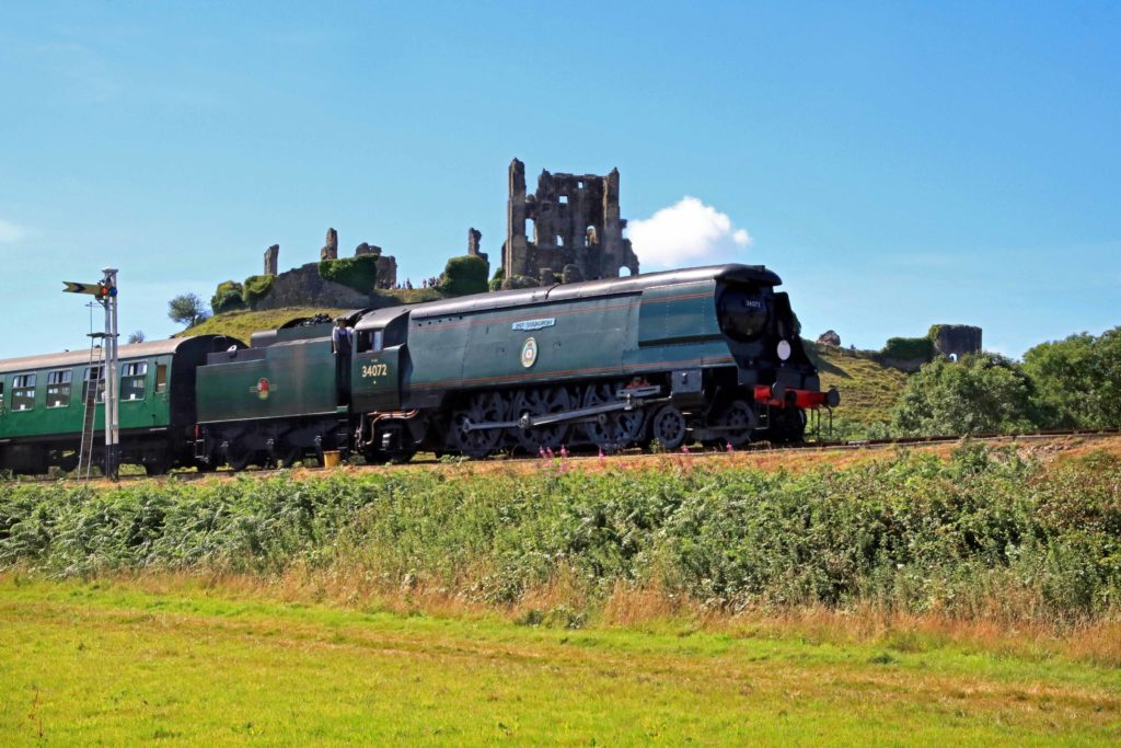 Train going past Corfe Castle on Swanage Railway summer