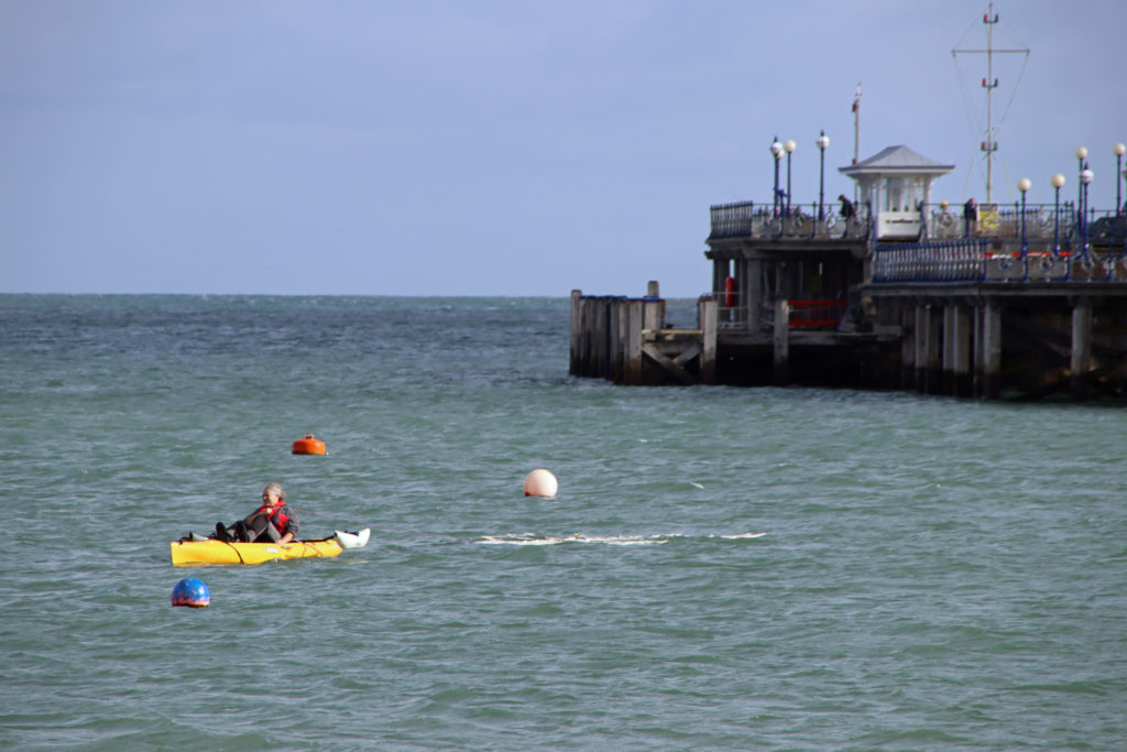 The Disappearing Fish installation being towed by a kayak across Swanage Bay
