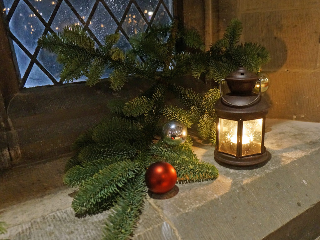 Lit lantern on window in St Mary's Church at Christmas
