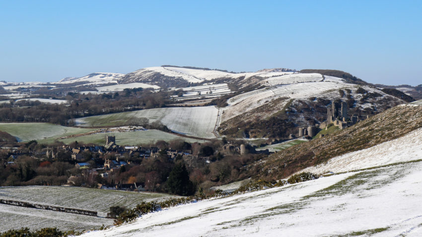 Snow on hills with Corfe Castle