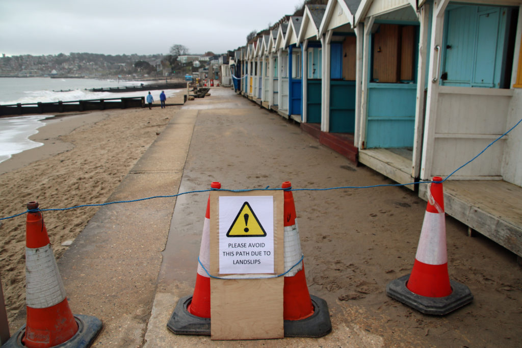 Warning sign by beach huts affected by landslip
