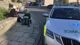 Ambulance car paramedic treating woman who had fallen over