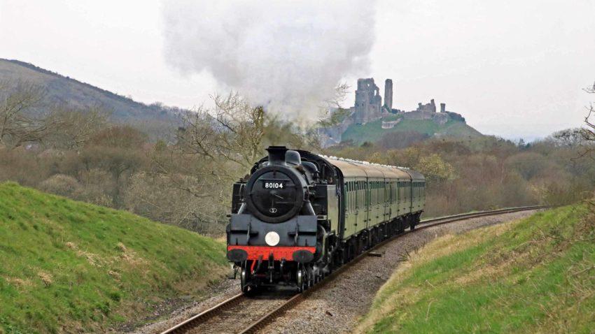 Steam train passing Corfe Castle