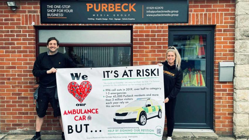 Purbeck Media staff with campaign banner