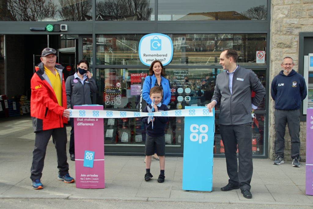 Zack cuts the ribbon to mark the relaunch of the Swanage Co-op