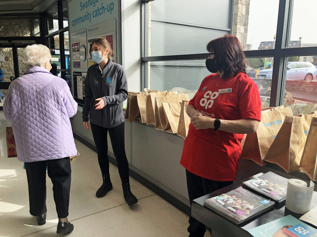 Handing out goodie bags at the relaunched Co-op in Swanage