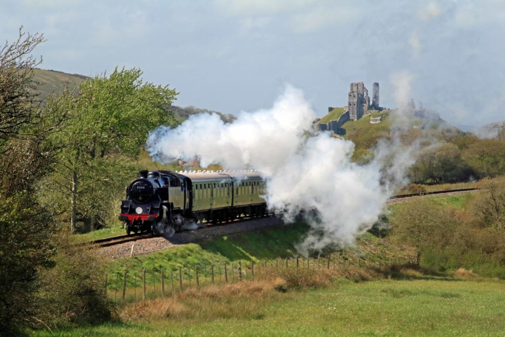 Locomotive pulling carriages through Purbeck countryside