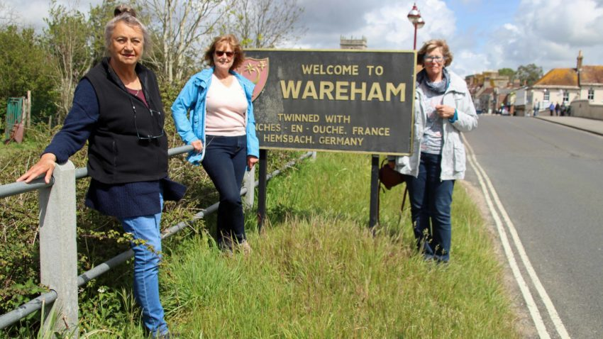 People next to Welcome to Wareham sign