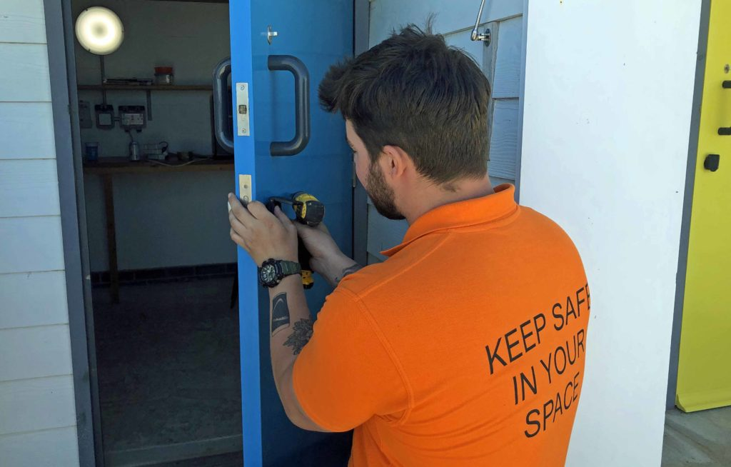 Swanage Beachfront advisor mending lock on beach hut