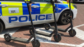 Three e-scooters next to police car