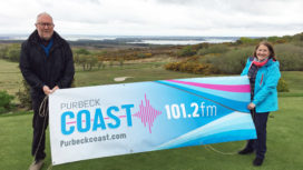 Sports presenters with Purbeck Coast banner on golf course